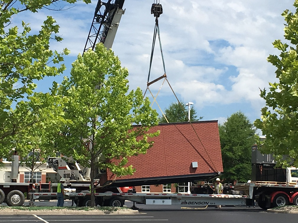 Hut being lifted off flatbed truck